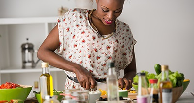 woman prepping food items in a kitchen smiling