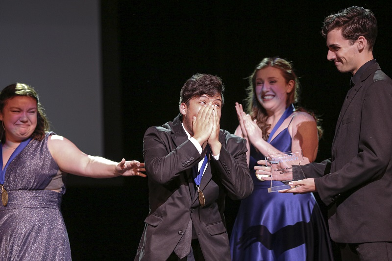 A young man in a suit is surprised on stage, while a group of his peers celebrate him.