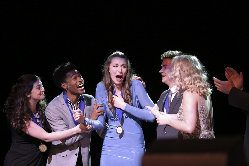 A young woman in a periwinkle dress cries tears of joy when she is surprised with an award on stage. Her peers surround her in celebration.