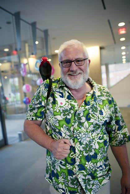 A man in a green, floral shirt smiles with a fake parrot on his shoulder