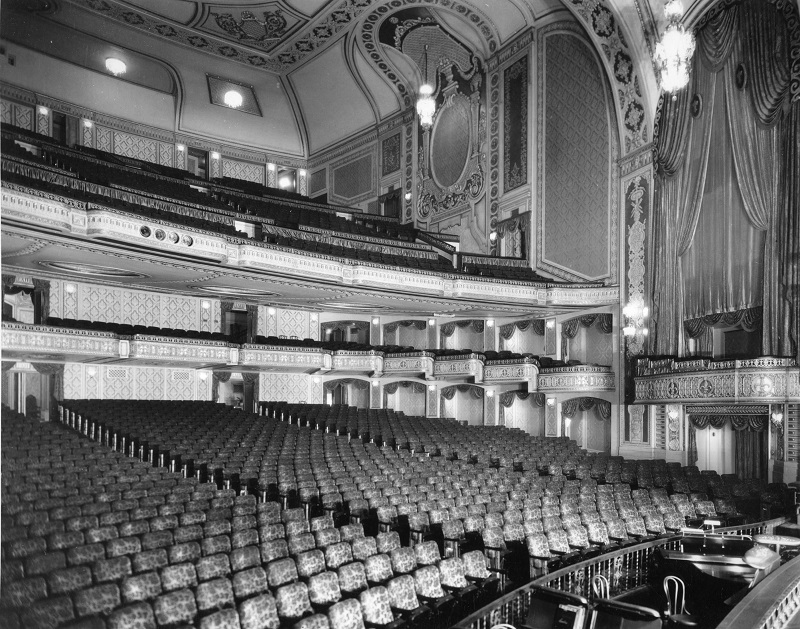 A black and white photo of the Orpheum Theater from 1928. Ornate seats and curtains adorn the concert hall