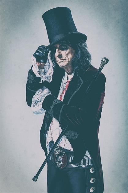 A man wears a top hat, velvet coat, lace shirt and carries a cane with a skull on top