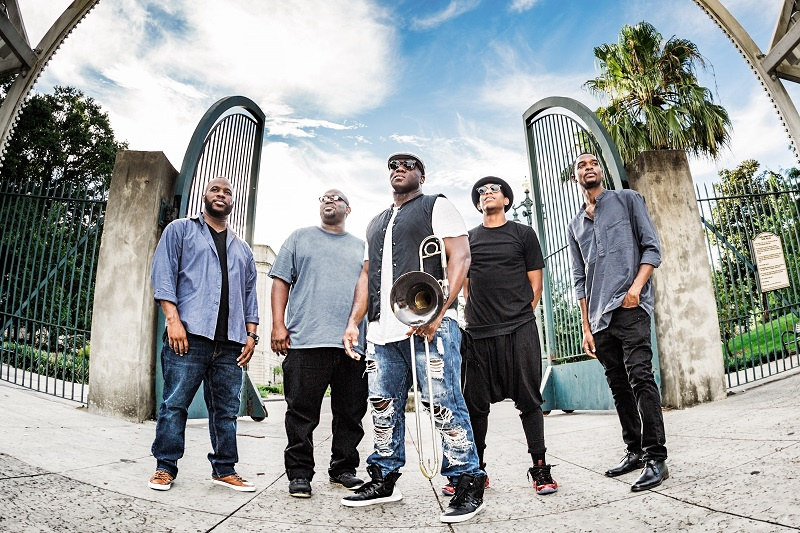 5 African American men stand together, one in the middle with a trombone, all wearing casual clothes like jeans and t-shirts.