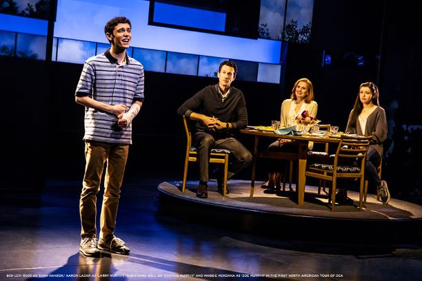 A boy in a striped shirt and arm cast sings on stage with a family at the dinner table in the background