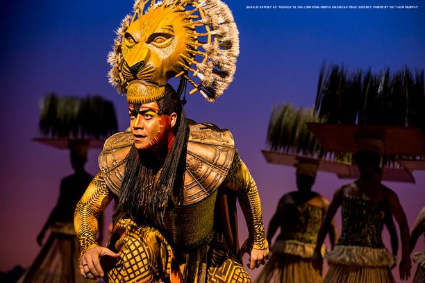 An actor with a lion headdress plays Mufasa on stage