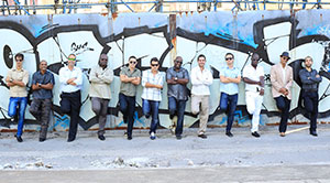 members of havana cuba all starts standing in front of a wall with various instruments
