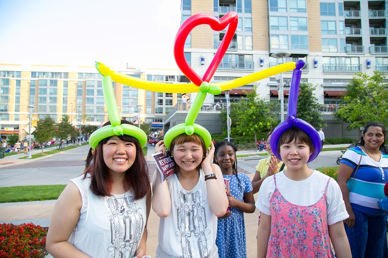 Three girls share a balloon hat, smiling and laughing