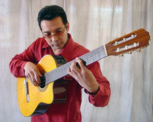 Marcos Mora, dressed in a red shirt and sunglasses, plays the guitar.