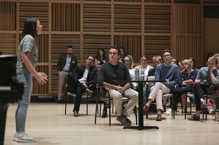 Brian d'Arcy James sits at a small table in the Scott Recital Hall as a student sings a song for the whole room. Students watch from their seats behind Brian.