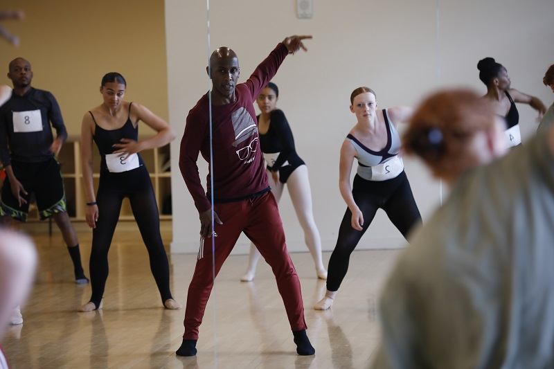 Ray Mercer stands in front of a mirror in a dance studio as dancers in leotards mimick his movements behind him