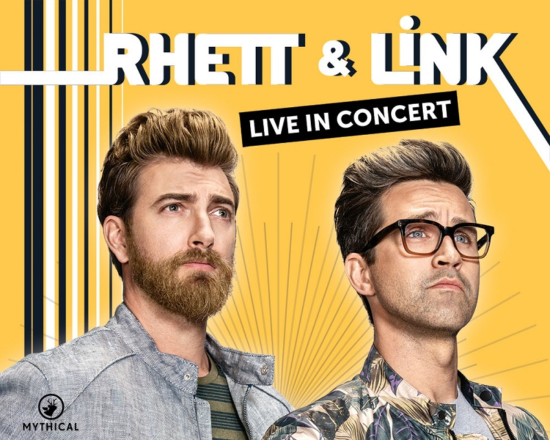 "A blonde man and a brunette man with glasses stare off into the distance triumphantly. Text reads: ""Rhett and Link Live"""