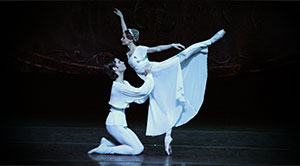 man and woman ballet dancers on stage performing
