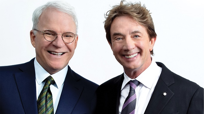 Steve Martin and Martin Short stand together for a photo. They're wearing suits, smiling, standing against a white backdrop.