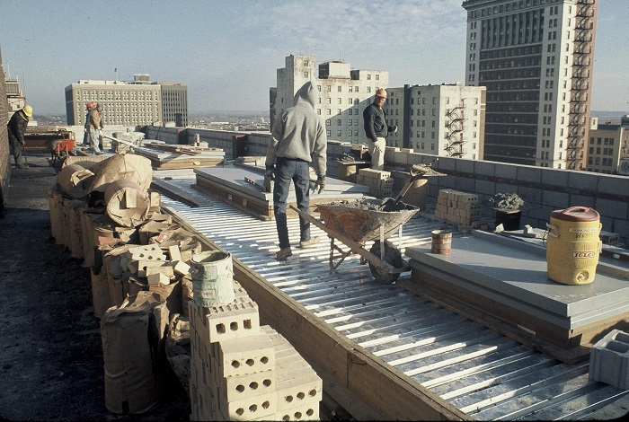 Men work on the roof of the theater. In the distance you can see the smaller Omaha skyline of the 1970s.