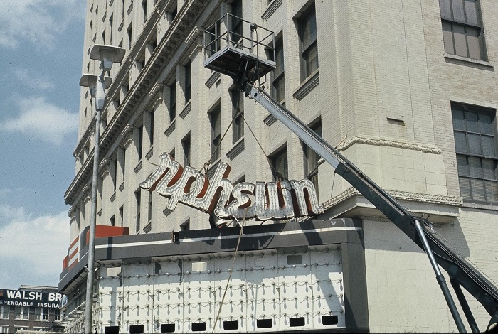 A crane removes the broken Orpheum lights sign from the marquee. The Orpheum was a movie theater before it became a performing arts center.
