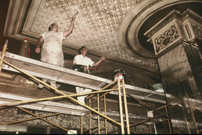 Two men stand on scaffolding to paint the faded ceiling of the Orpheum Lobby. The image is from 1974 and is faded.