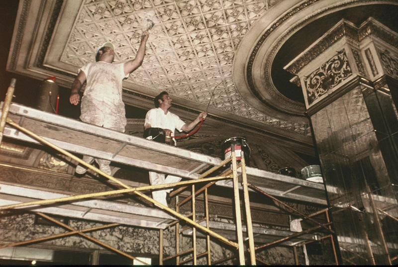 A rustic photo from the 70s shows two men working on construction in the Orpheum Theater