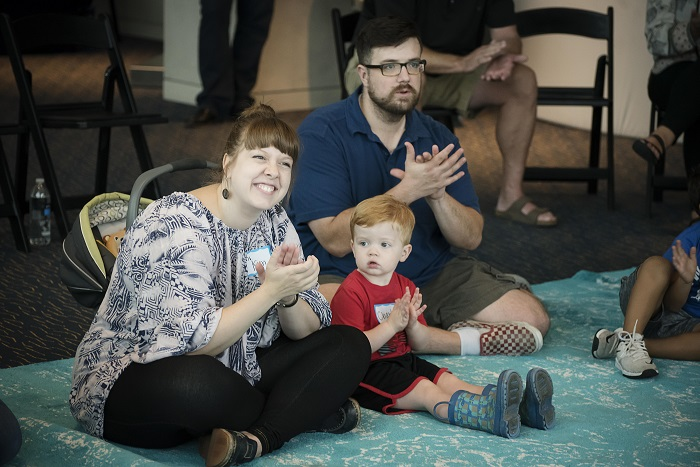 WeBop instructor and mom Kim Lomax sits cross-legged next to her toddler son. They're both clapping along to WeBop music with big smiles on their faces.